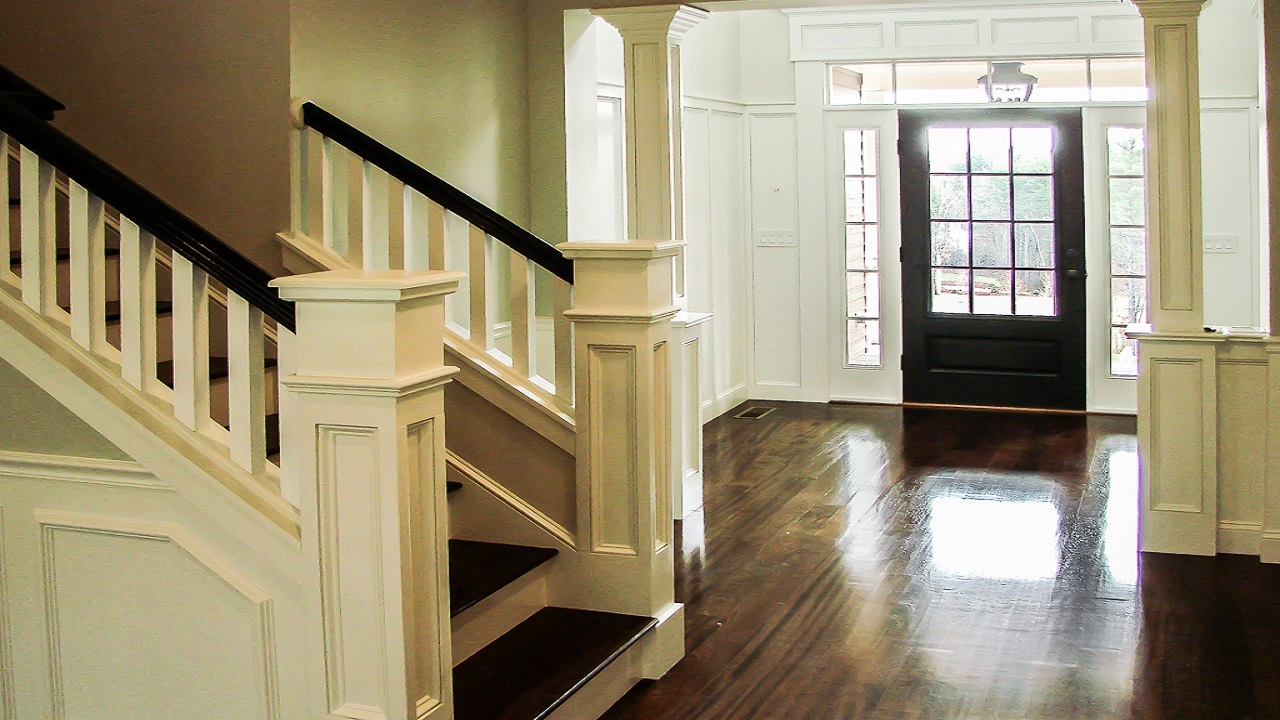 Stairs with square railing and posts, dark cherry treads and hardwood floors, doorway with richly trimmed square posts, transom lights around the entry door are all essential design elements in a crafstman home for sale in nh these days.