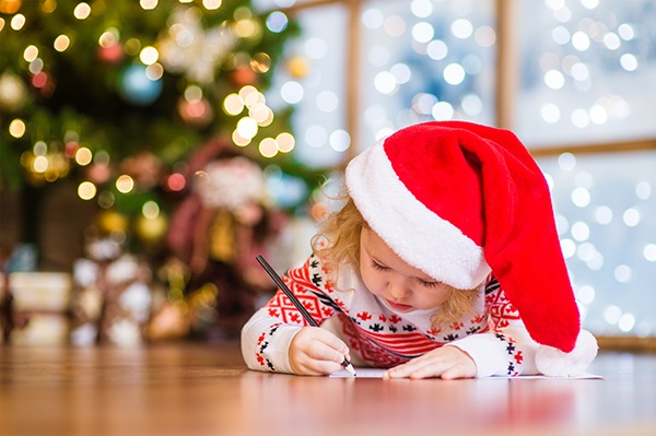 Little girl writing her Christmas list in a Santa hat